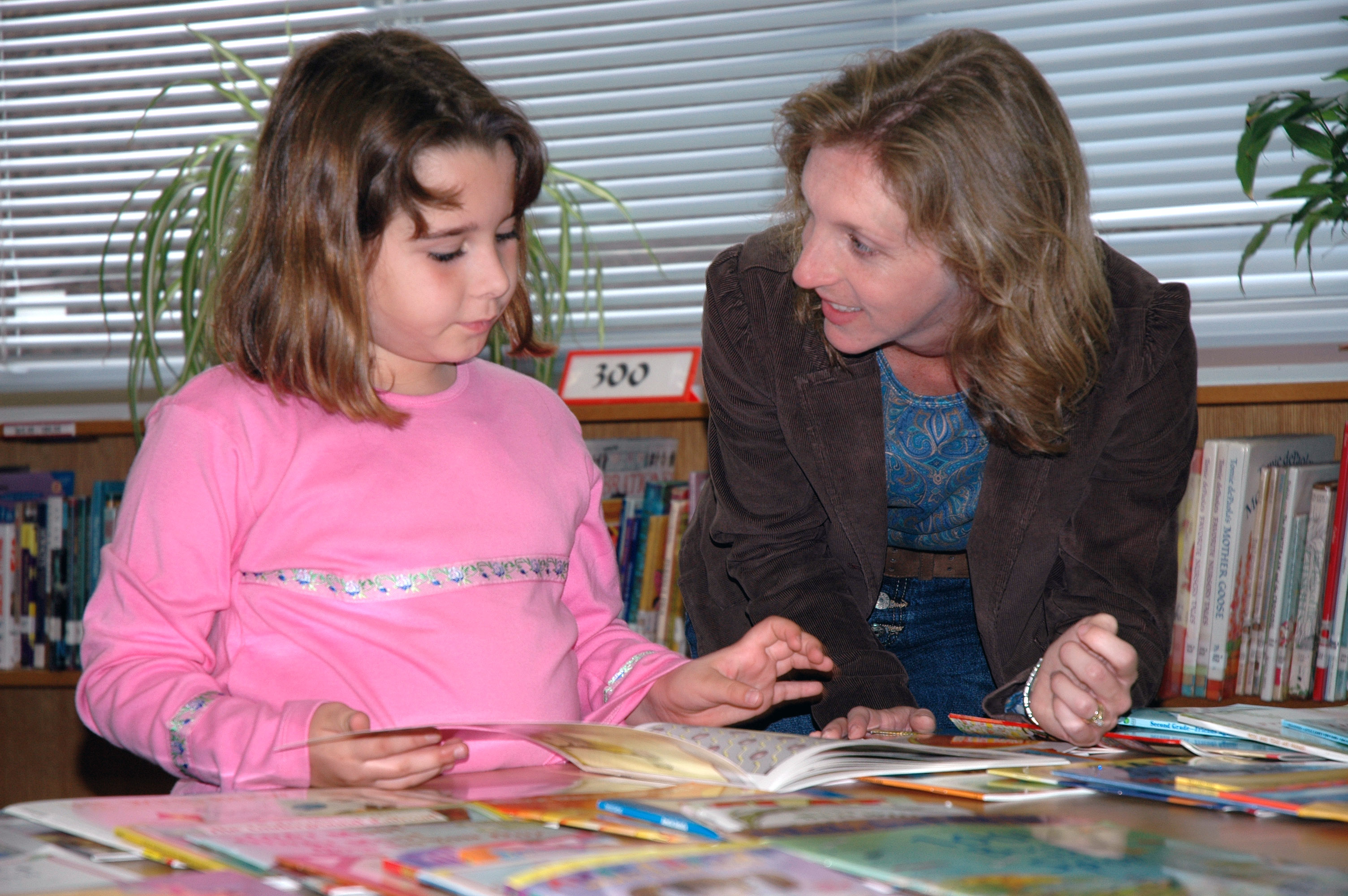 061026-N-5271J-014 Sasebo, Japan (Oct. 26, 2006) - Jennifer Tonder (right), a teacher's aide for a 3rd-4th grade multi-age class, discusses the various books available from the Reading Is Fundamental (RIF) grant given to Sasebo Elementary School with a student. The RIF donated 1,000 books to the school's library. Sasebo Elementary was the first overseas school to receive the RIF grant. U.S. Navy Photo by Mass Communication Specialist 3rd Class Jeff Johnstone (RELEASED)